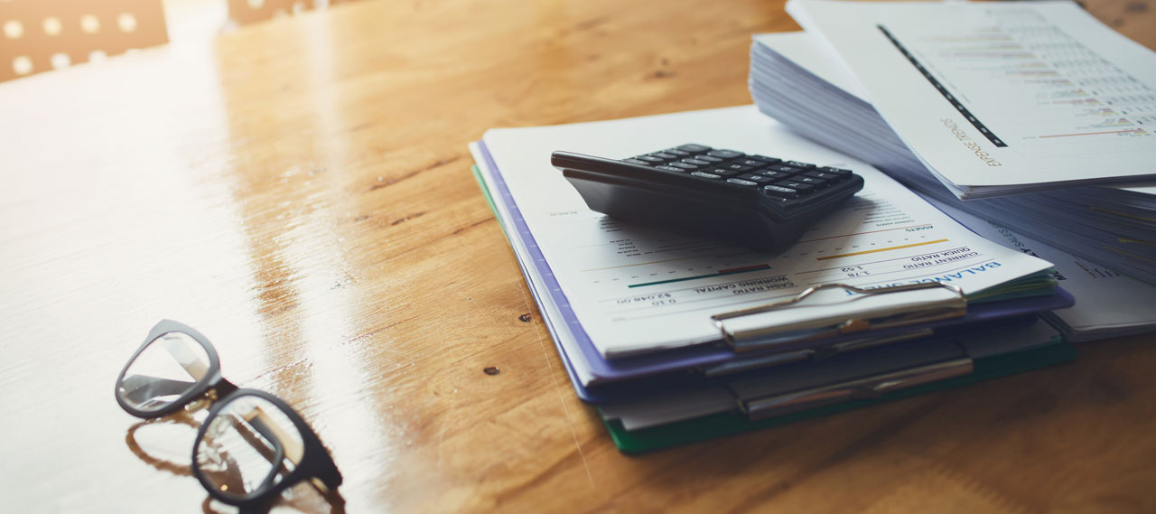 A pair of glasses and a notepad sitting on a desk.