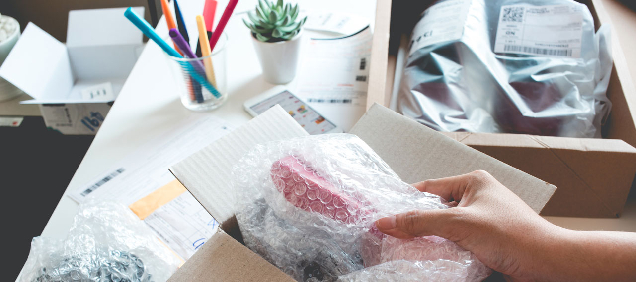 Items in bubble wrap being packed in a cardboard box.